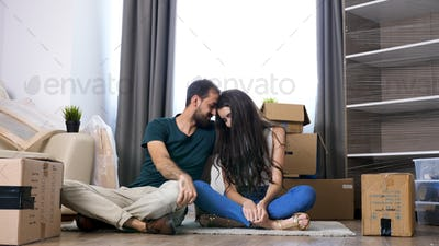 Young couple moving in new home. Sitting on floor and relaxing