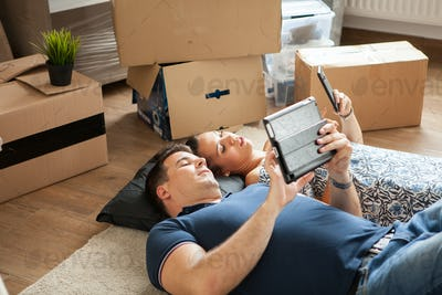 Happy young couple lying on floor near moving boxes.