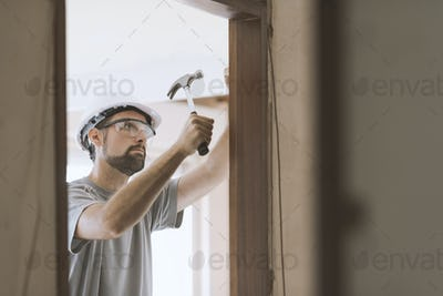 Carpenter installing a door jamb at home