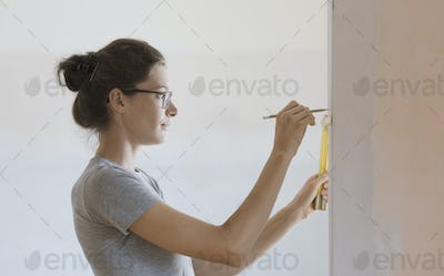 Woman doing a home renovation and measuring walls with a ruler