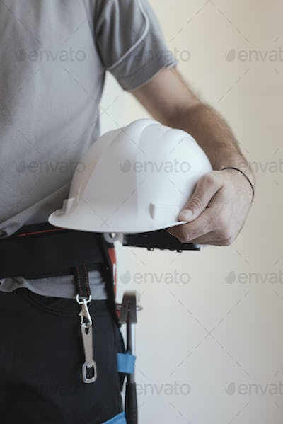 Construction worker holding a safety helmet
