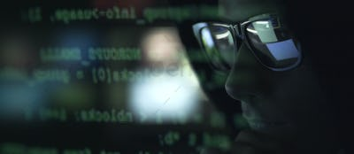 Hacker with sunglasses and code on the screen