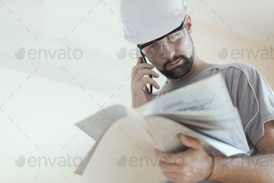 Professional construction worker checking a project and calling