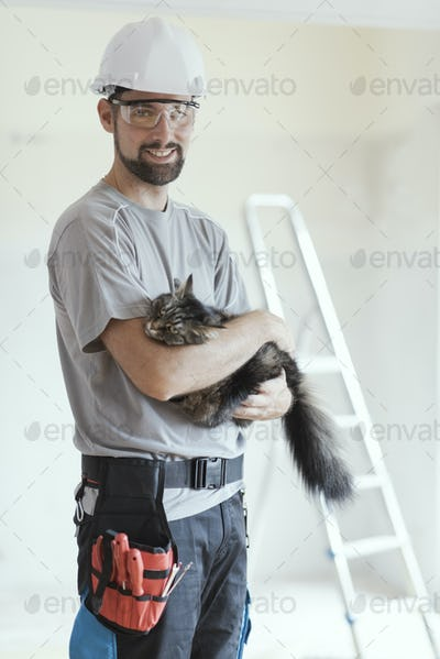 Repairman posing and holding a beautiful cat