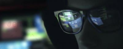 Nerd hacker with glasses in the dark