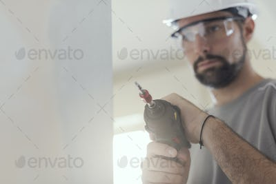 Professional construction worker using a drill