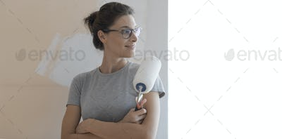 Confident happy woman painting walls at home