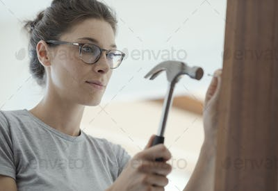 Carpenter woman repairing a door at home