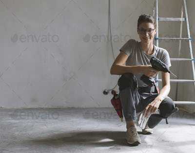 Professional repairwoman posing and holding a drill