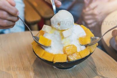 Group of people enjoy eating mango bing su, Korean dessert
