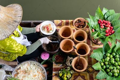 Market woman in boat cooking food at floating Market in Bangkok, Thailand