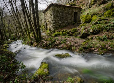 Rural stone house next to a stream