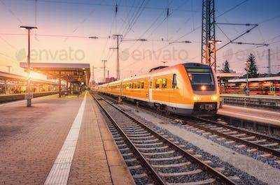Orange high speed train on the railway station at sunset