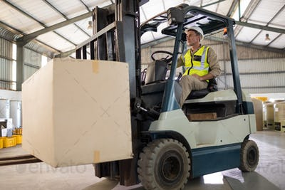 Worker carrying package with forklift