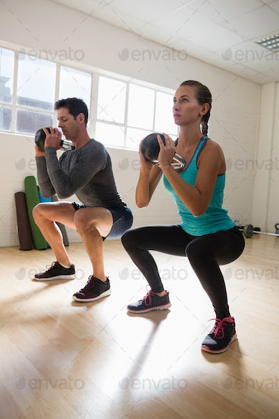Full length of athletes exercising with kettlebells