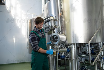 Male worker taking beer from storage tank at factory