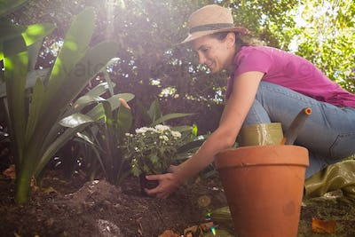 Side view of smiling woman planting flowers while crouching