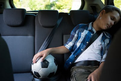 Teenage boy sitting with football in the car