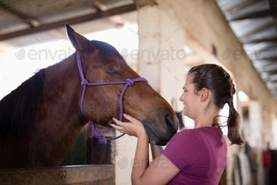 Side view of female jockey holding horse head