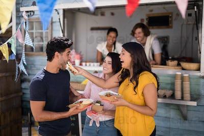 Smiling friends eating snacks