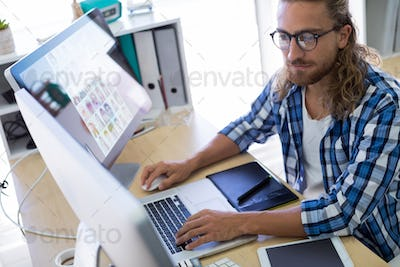 Male executive working over laptop at his desk