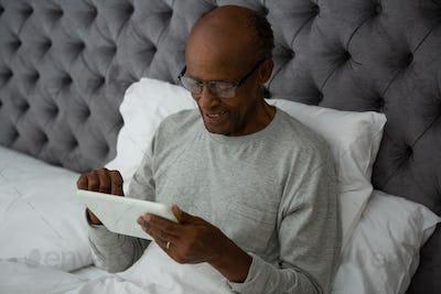 Smiling senior man using digital tablet while resting on bed