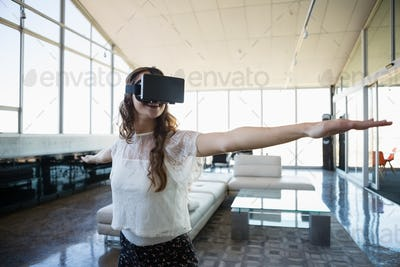 Smiling businesswoman using virtual reality simulator exercising in office