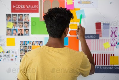 Rear view of man pointing at sticky note in office