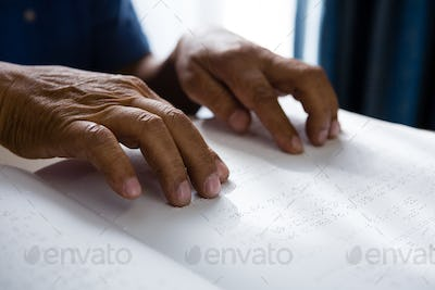 Cropped hands on retired man reading braille book in retirement home