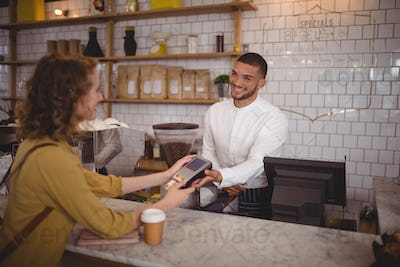 Smiling young woman paying through card to waiter at counter