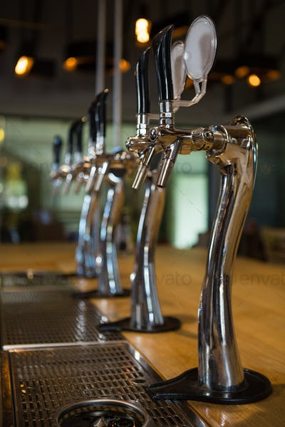 Beer taps in row at bar