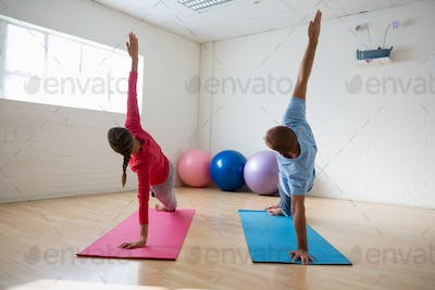 Instructor with student practicing side plank pose in yoga studio