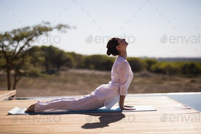 Woman practicing yoga on at poolside