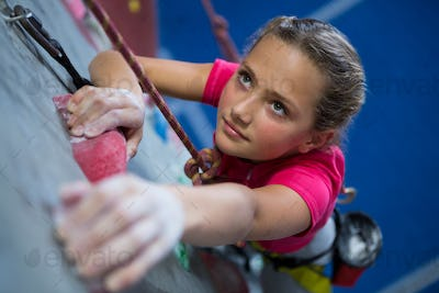 Determined teenage girl practicing rock climbing