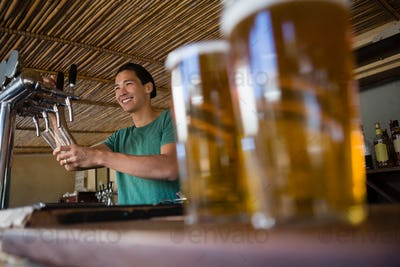 Close-up of beer glasses with bartender looking away