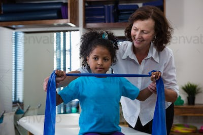 Physiotherapist assisting girl patient in performing stretching exercise from resistance band