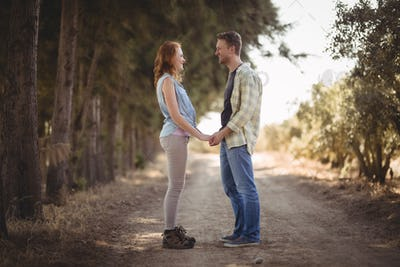 Young couple holding hands while standing on dirt road at olive farm