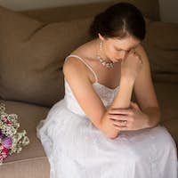 Sad bride sitting by bouquet on sofa at home