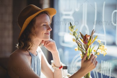 Smiling young woman looking at flower against window