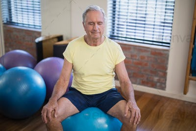 High angle view of senior male patient sitting on exercise ball with eyes closed