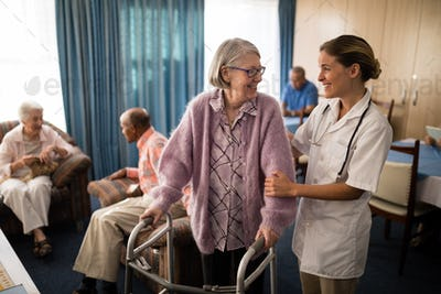 Smiling female doctor looking at senior woman standing with walker