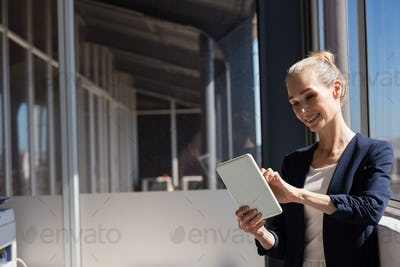 Smiling businesswoman using digital tablet while standing by window