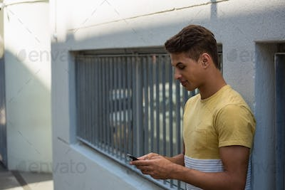 Young man using mobile phone while leaning on wall