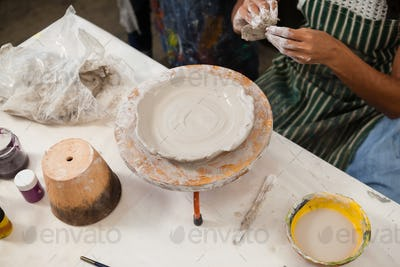 Mid section of woman learning pottery
