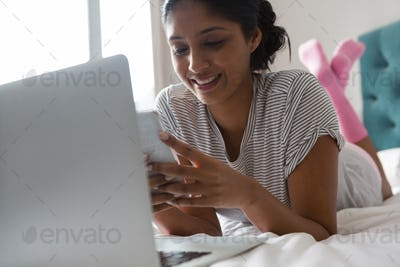 Smiling woman with laptop using phone on bed