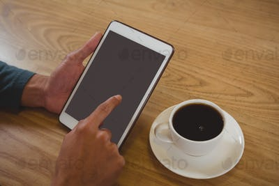 Cropped hands of man with coffee using tablet in cafe