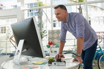 Smiling designer using computer while standing at desk