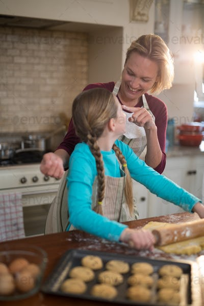 Happy mother and daughter having fun while preparing cookies in kitchen