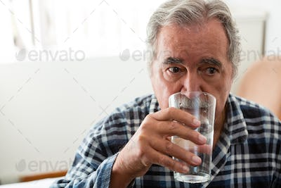 Senior man drinking water in nursing home