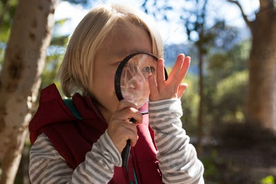 Smiling girl looking at a hand through a magnifying glass